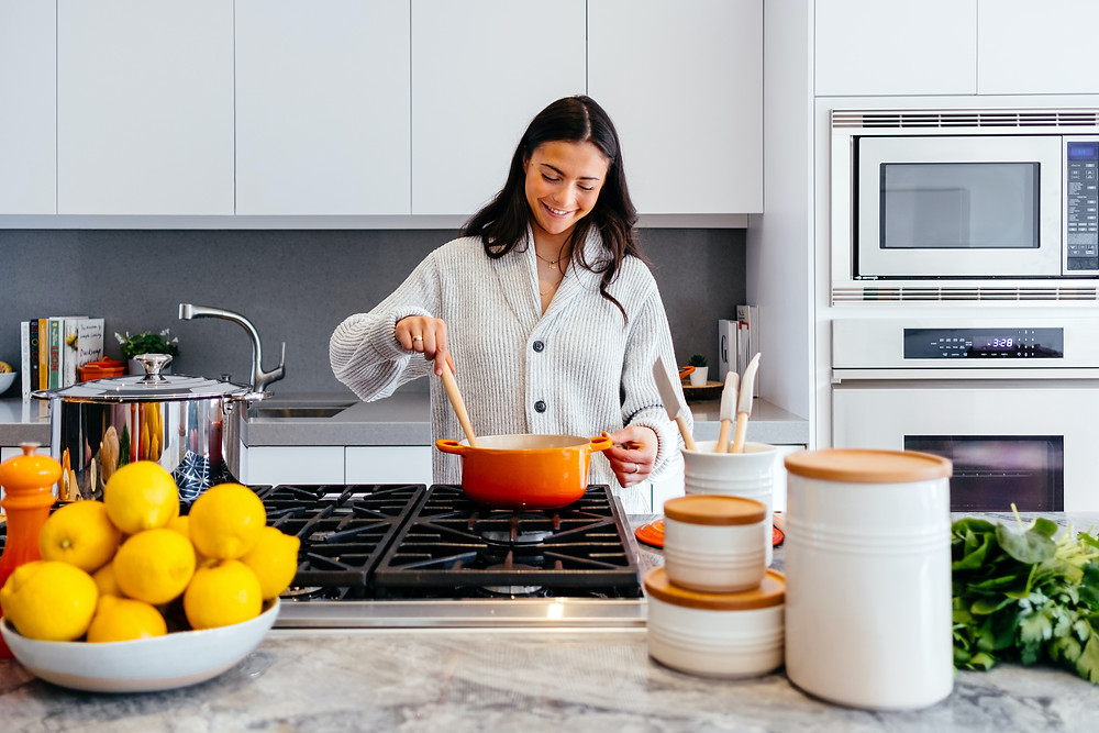 a woman with black hair cooking a healthy meal in the kitchen