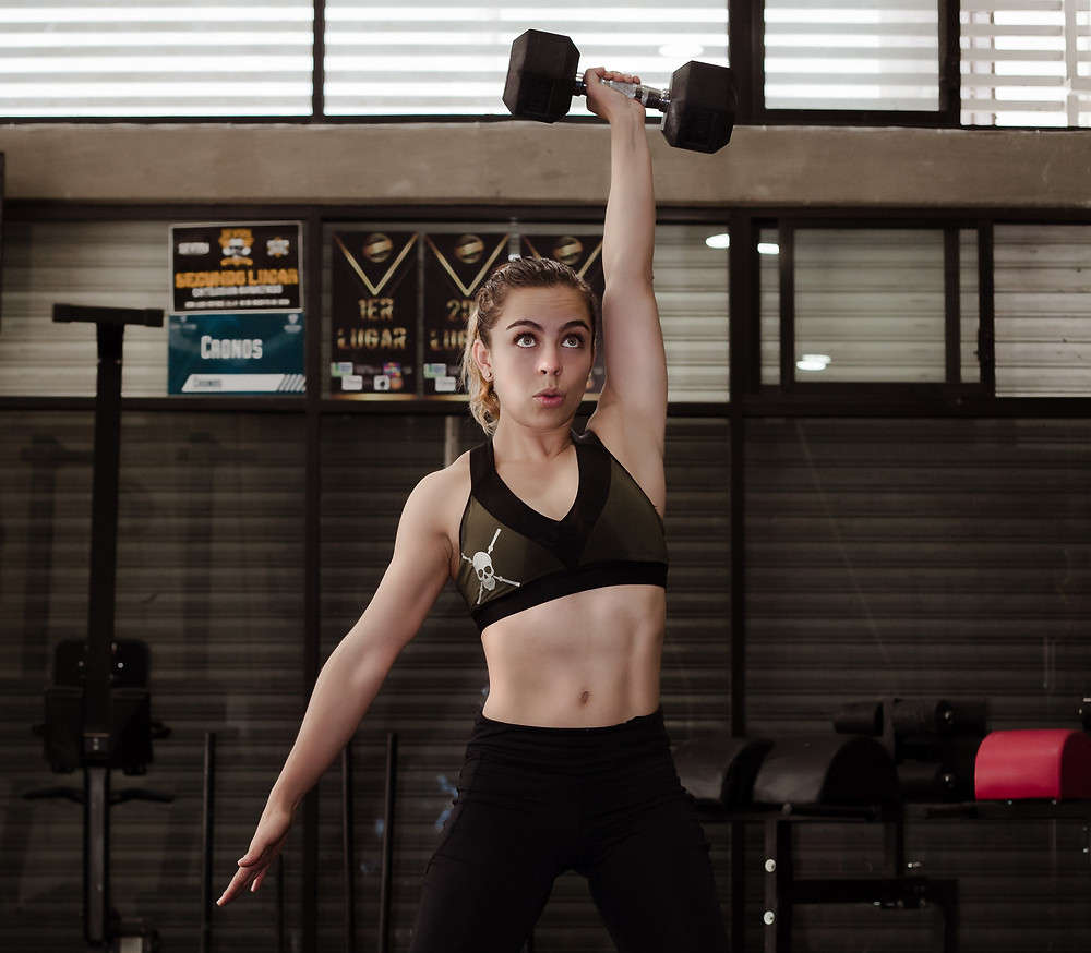 a woman lifting a dumbbell above her head