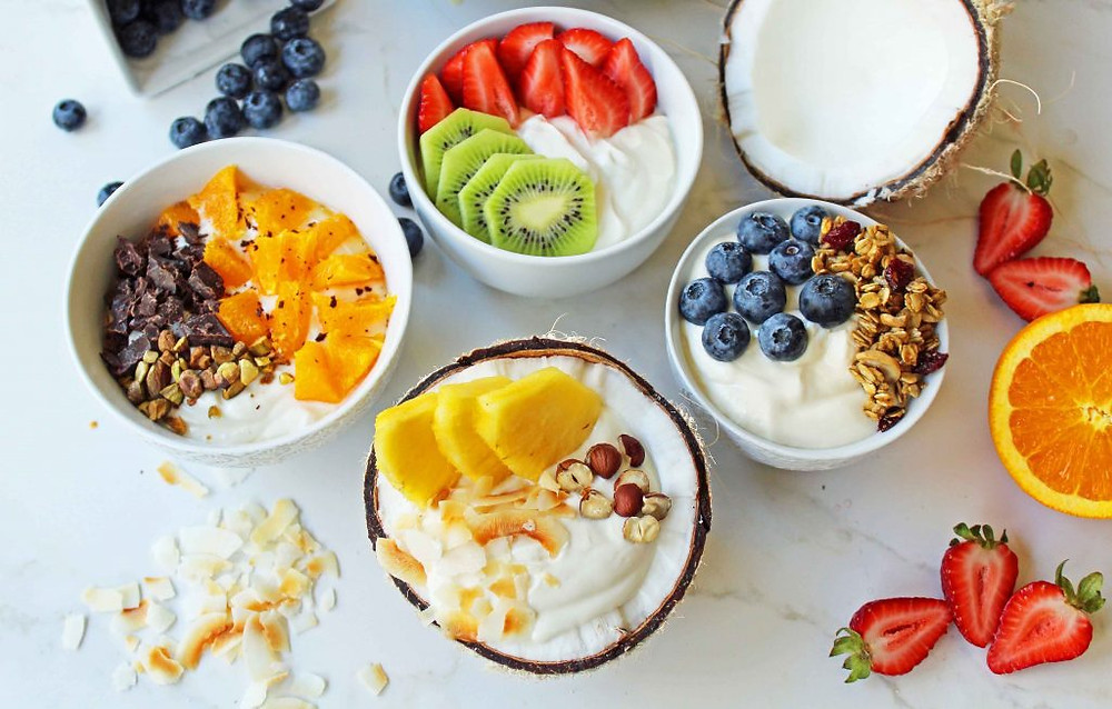 a breakfast table full of fruit and bowls of yoghurt