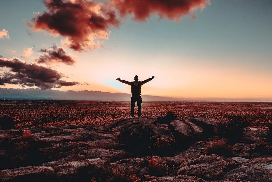 a man standing with arms wide in a field with red sky