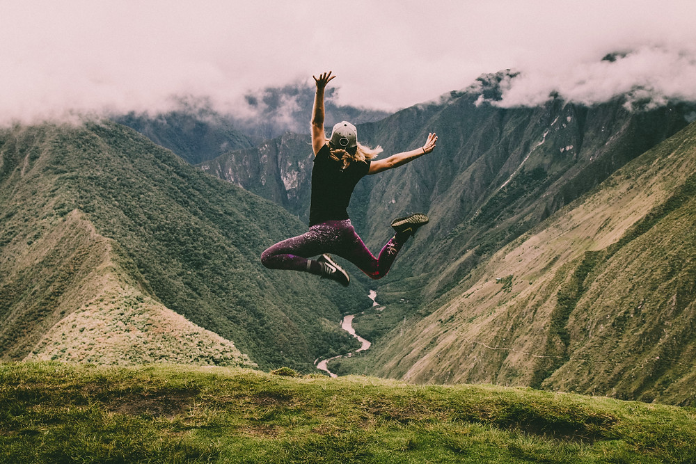a woman jumping on top of a mountain