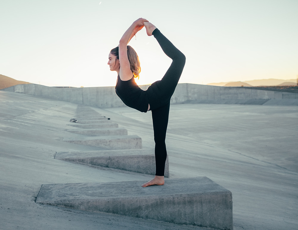 lady stretching outdoors in black leggings