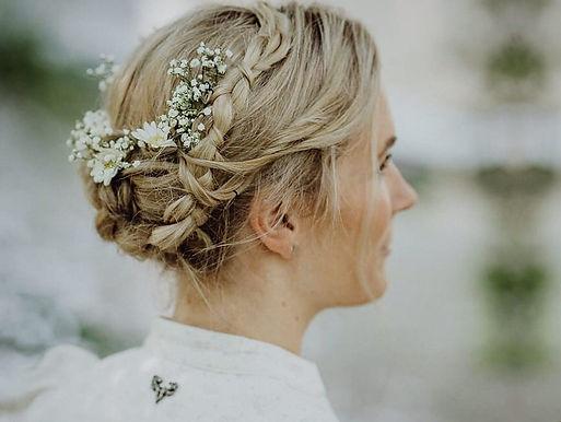 Eine blonde Braut mit traditioneller Flechtfrisur