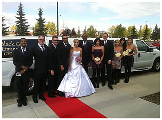Wedding party in front of Black Gold Limousine