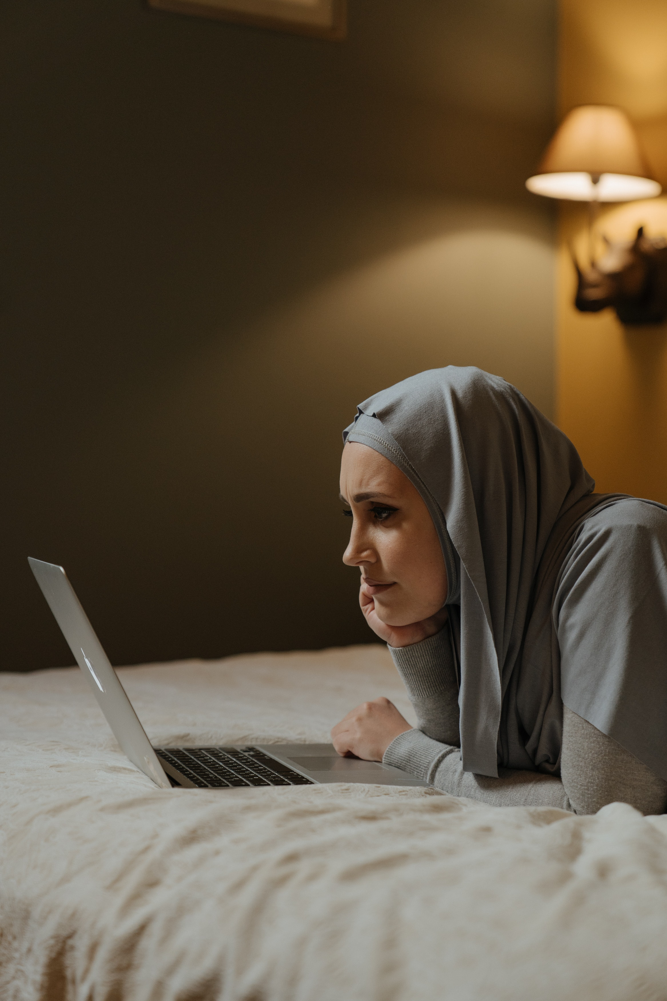 A Person of Colour wearing a grey headscarf looking at a laptop on a bed. They look engrossed.