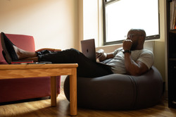 A Black person sits on a beanbag, feet on a table, looking at a laptop hand slightly clenched.
