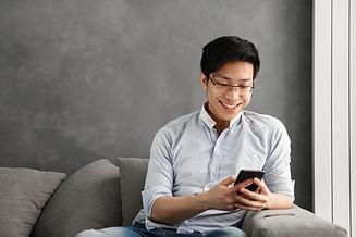 Portrait of a happy young asian man using mobile phone while sitting on a couch at home.jp
