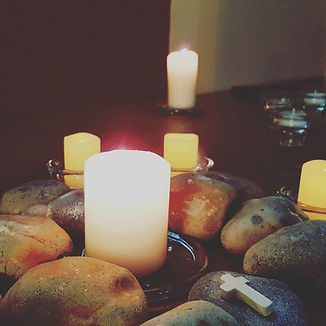 An arrangement of large pebbles and lit candles, with a small cross laid on one of the pebbles