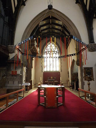 The altar decorated for Pentecost, with red hangings and red and yellow ribbons hanging from the frame above.