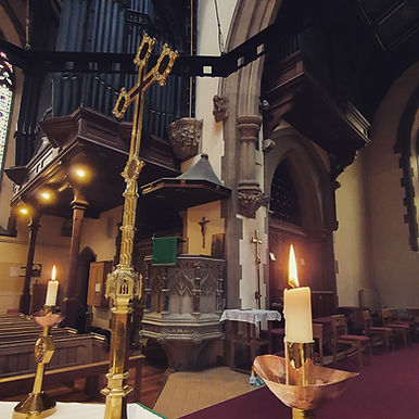 Inside St John's church with cross and candlesticks in the foreground and the pulpit and organ in the background.