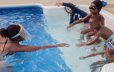 Paulana teaching black kids to swim.