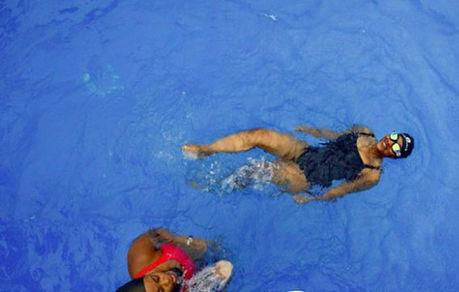 Two women swimming in pool