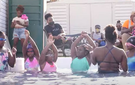 African American swim coach teaching black girls how to swim