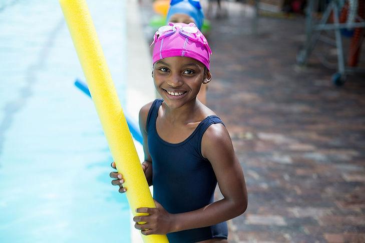 little black girl holding pool noodle at