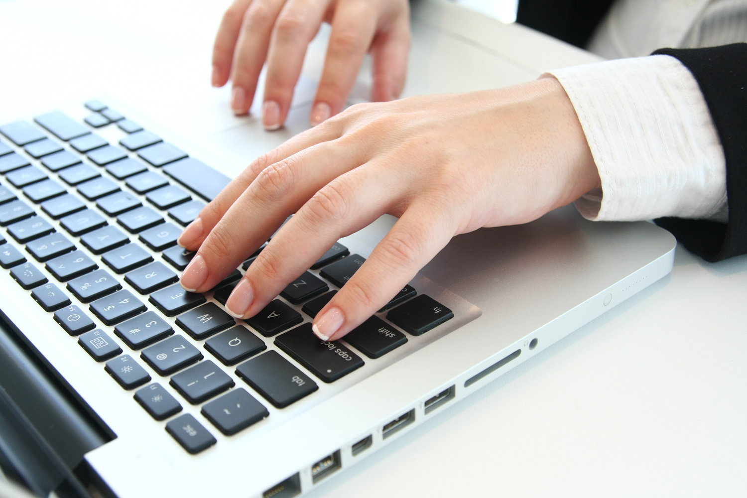 A hand typing on a compuer