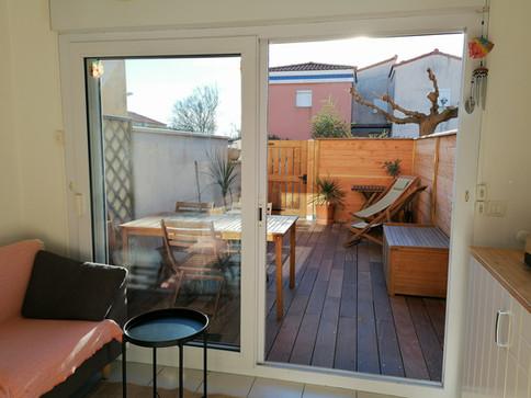 Coin salon et cuisine donnant sur une terrasse