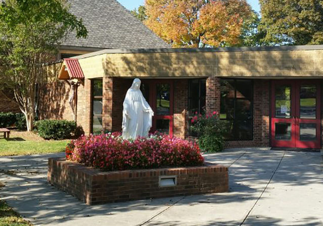 front entrance of Our Lady of the Assumption Catholic Church with a statue of Mary surrounded by red flowers