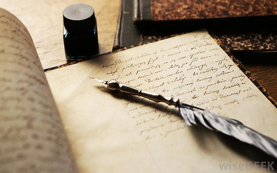 Quill and journal with inked words across the page.