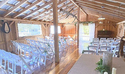 Upstairs of the barn venue with white chairs and arbor for wedding ceremony.jpg