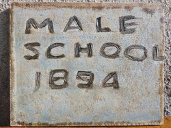 The plaque on the wall by the entrance to the old school
