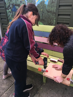 Kate assisting Claire to drill holes in
