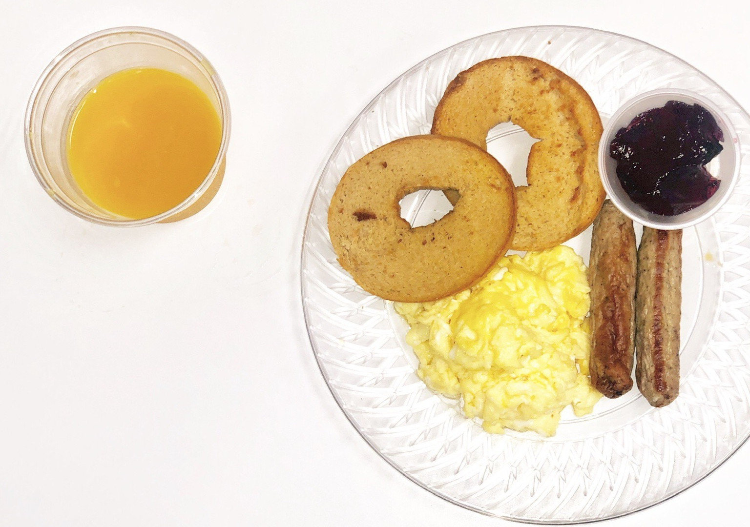 bagels with eggs and turkey sausage with a side of grape jelly and orange juice