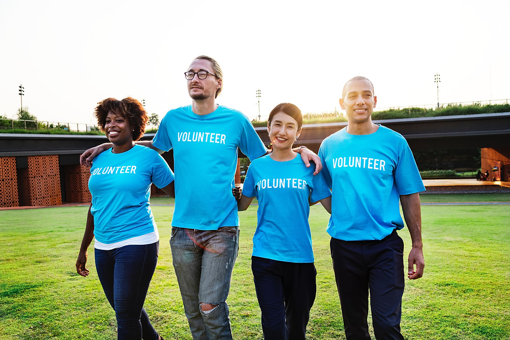 A group of 4 people arm in arm, smiling wearing volunteer shirts