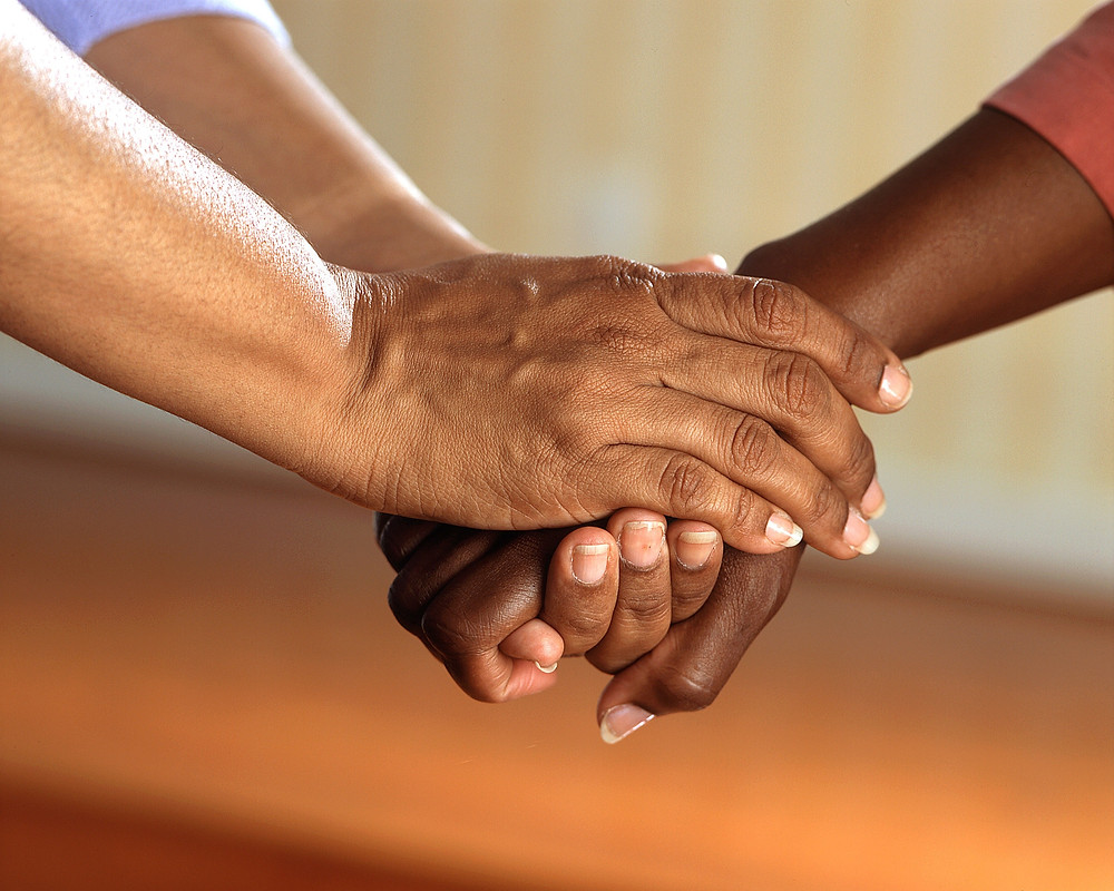 Two people holding hands comforting each other.