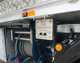 Hose reel with electric controls mounted under the body of a water truck