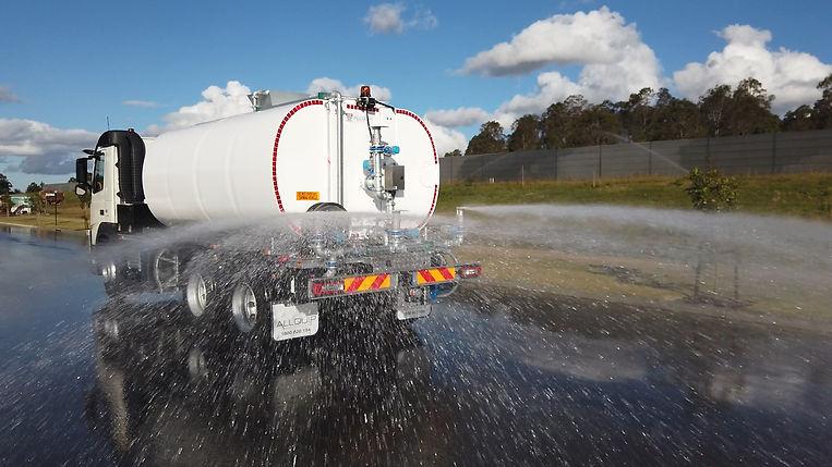 Water truck in action with rear fan sprays