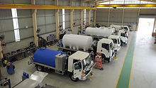 Allquip's assembly warehouse with water trucks and slide-in tanks
