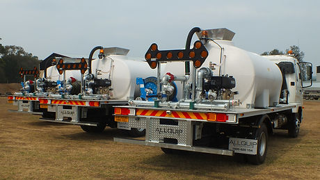 Three identical water carts lined up displaying spray systems and arrow boards