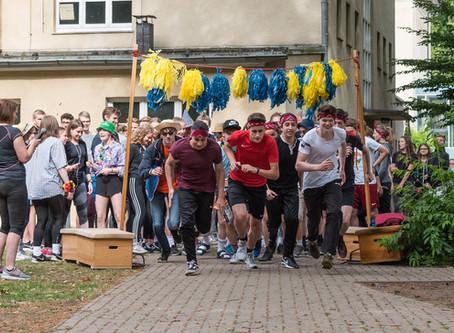 Schüler und Lehrer schnüren Laufschuhe für benachteiligte Kinder