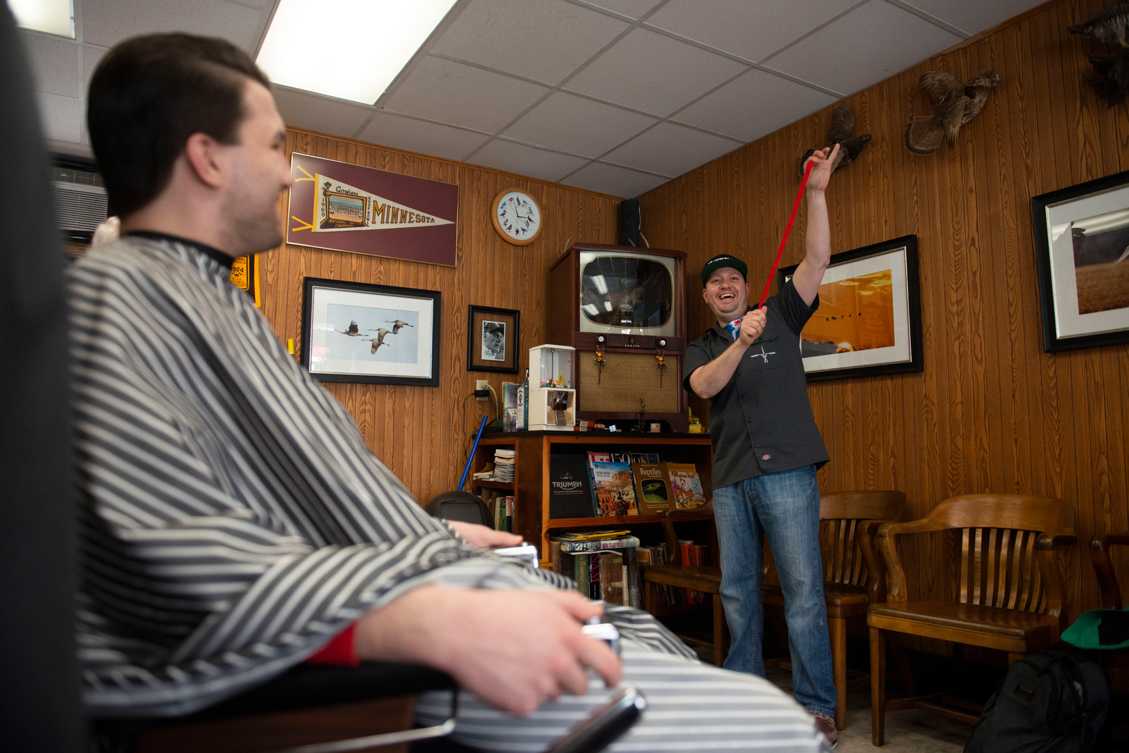Dan Griffin performs a magic trick for customers at Craig's Como Barbershop on Friday, April 26, 2019.