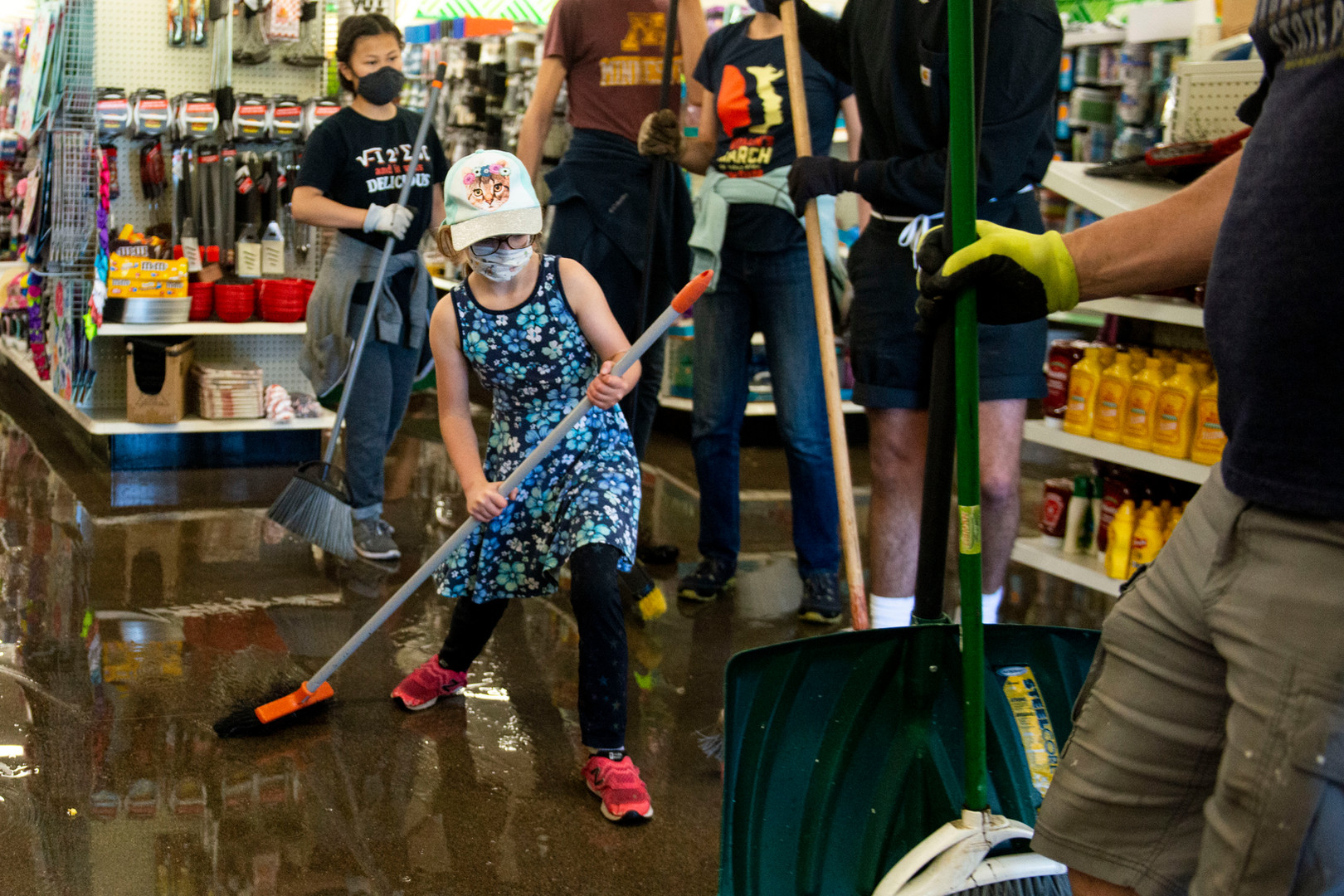 Abby Friedman (9) helps to sweep water out of Dollar Tree near the Minneapolis 5th precinct following another night of riots on Friday night.