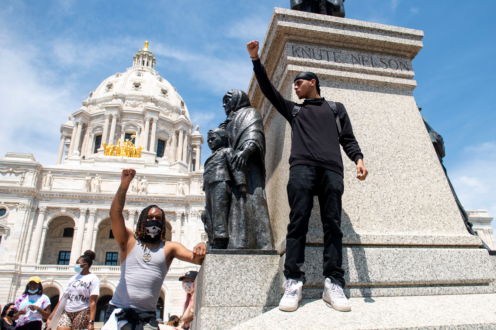 Xavier Hayden, left, and Ty Henderson, right, raise their fists at a student-organized rally outside the Minnesota State Capitol on Tuesday, June 2.