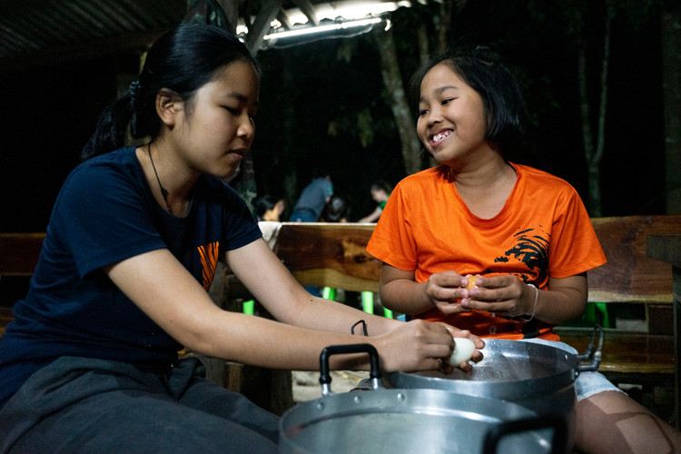Kanokwan Baiya, left, and Nawapat Simcharoen (10), right, prepare hard boiled eggs on the eve of her tenth birthday. The daughter of Saksit and Achara Simcharoen, she has grown up in the sanctuary learning from Thailand's top tiger biologists.