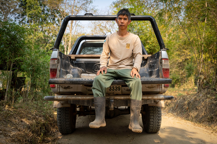 Onsa Norasarn, a Huai Kha Khang field technician of over 10 years, poses for a portrait on the back of a truck after a day's work.