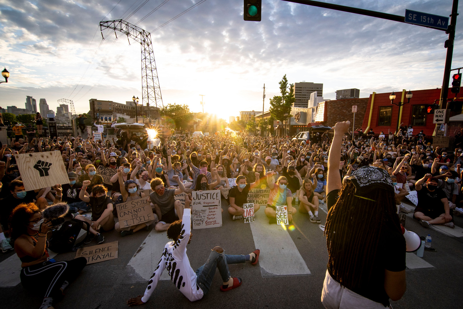 A group of mostly University of Minnesota students raise their fists during a protest held at the intersection Southeast 4th Street and 15th Avenue Southeast on Wednesday, June 3.