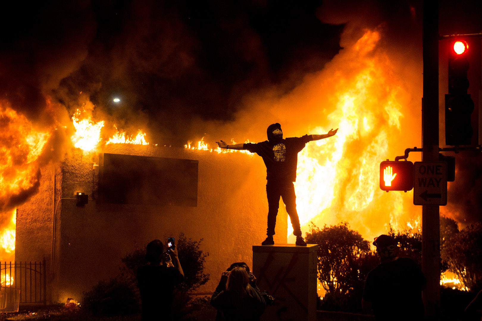 Photos are posed for in front of a burning building as part of riots near the 5th precinct in Minneapolis on Friday, May 29.