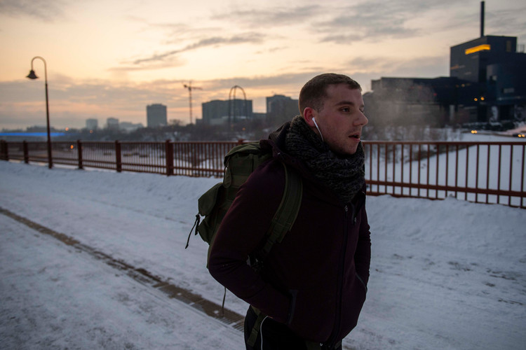 Diamond carries a 50-pound pack as part of an early morning training ruck through Minneapolis. The Guthrie Theater, seen behind him, was largely influential his decision to move to Minneapolis to join its acting community. Five years later, that community still remains a part of him as he shifts his personal and professional aspirations.