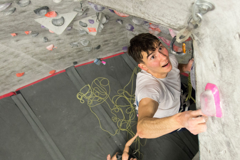 Michael Laraia eyes his next hold as part of a lead climb during practice with the University's climb team on Tuesday, Nov. 13.
