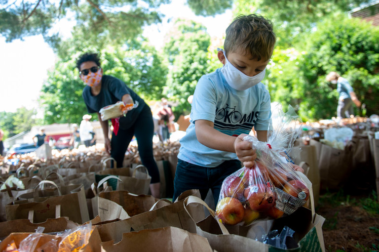 Harris Larmon (4) helps his mom, Erika, organize donated goods at Sanford Middle School in Minneapolis on Sunday, May 31.