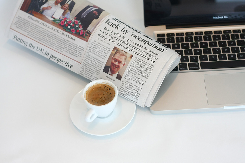 Newspaper sitting on table next to coffee and laptop