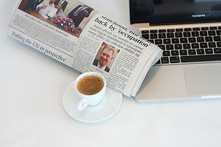 Cup of coffee, newspaper and laptop