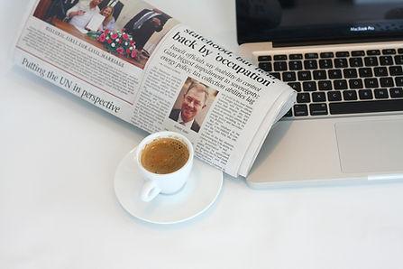 Escritorio con un ordenador, un periódico y una taza de café