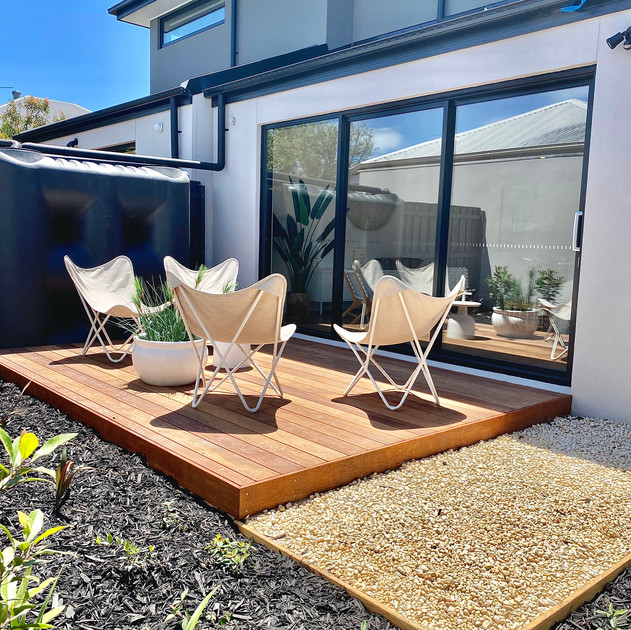 Merbau decking with timber edged black mulched garden beds and river pebbled pathway
