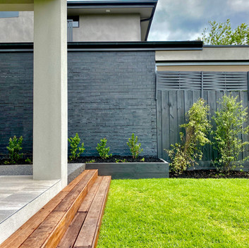 Turfed backyard area leading up Merbau steps into paved alfresco area