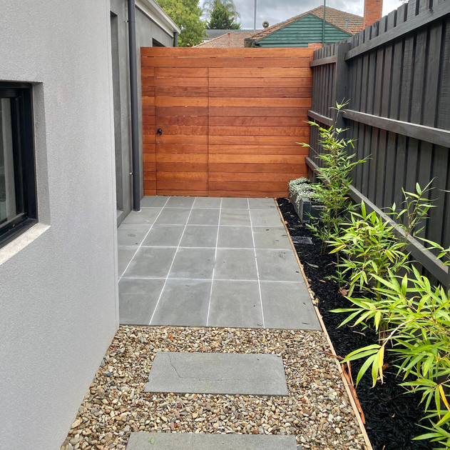 Bluestone paved area, Bluestone stepper path with river pebbles and Merbau gate and screen