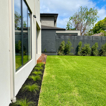 Timber edged garden beds in fluffy turfed backyard
